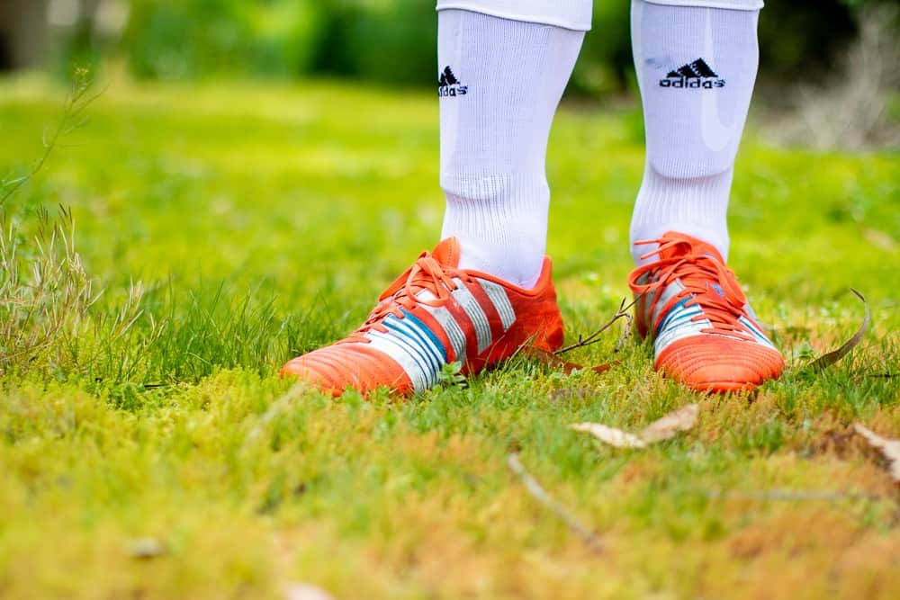 Close up of orange soccer cleats and socks