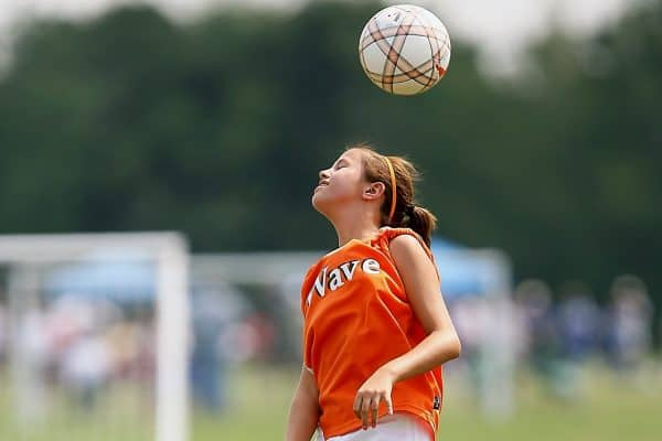 Girl in an orange soccer jersey is bouncing the soccer ball with her head