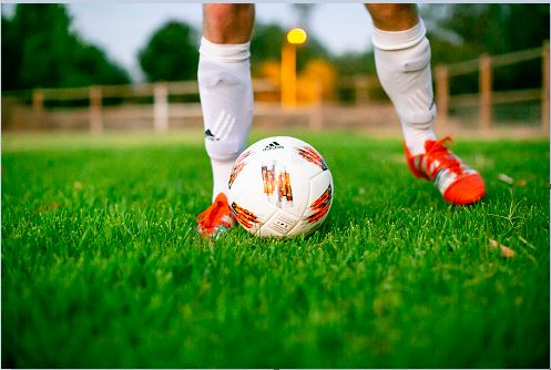 Man in white socks and orange soccer cleats with a soccer ball