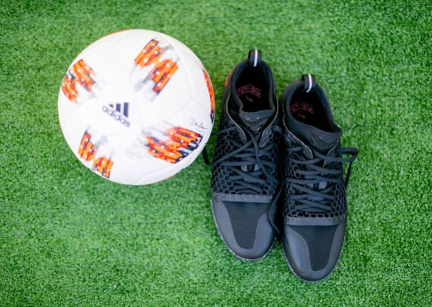 Top view of a black indoor soccer shoe and a white soccer ball