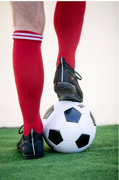 Man standing in red socks with a white and black soccer ball