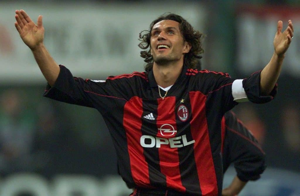 Paolo Maldini in a red and black soccer jersey raising his hands to the crowd