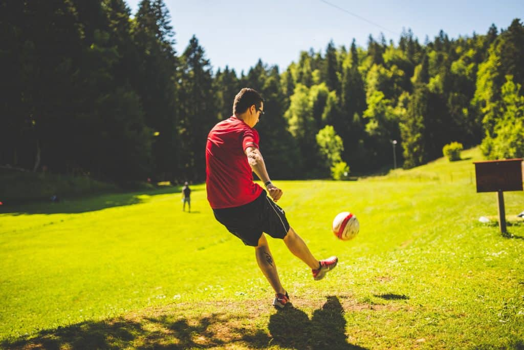 A man in a red shirt and dark colored shorts kicked the socker ball in an open grassy land