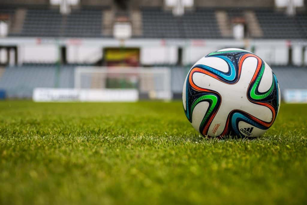 Colorful soccer ball in the middle of a soccer field granstand
