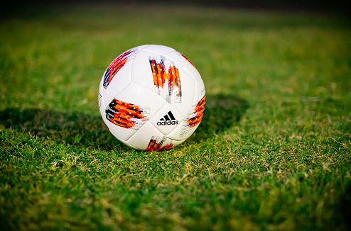 A soccer ball in the middle of the ground