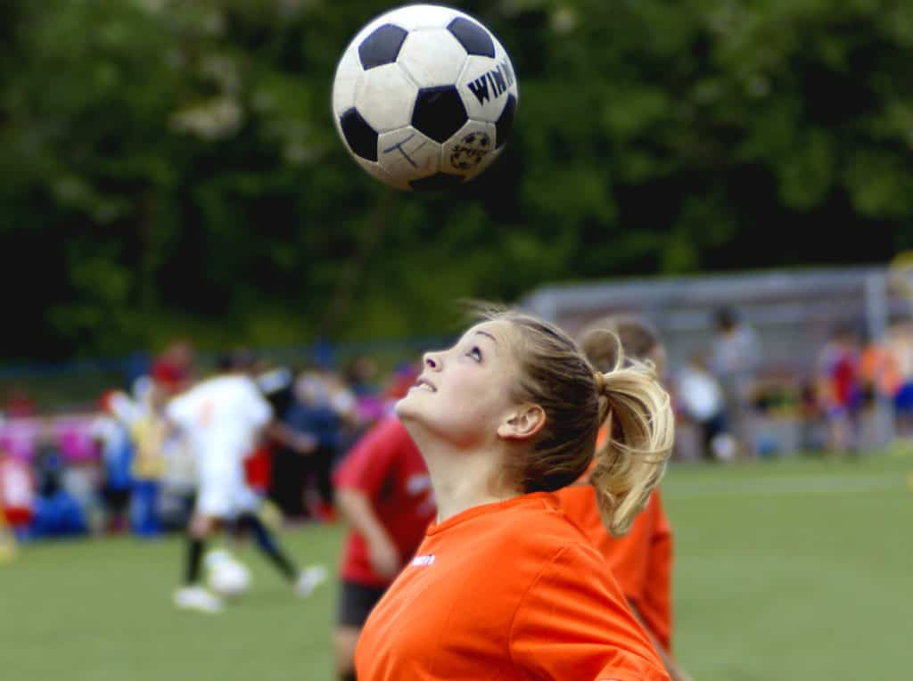 A girl in an orange jersey is looking at the soccer ball above her head