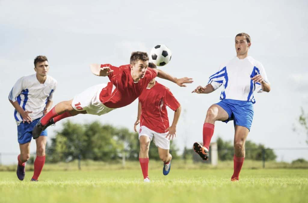 Man in red jersey jumps to do a diving header during a soccer match
