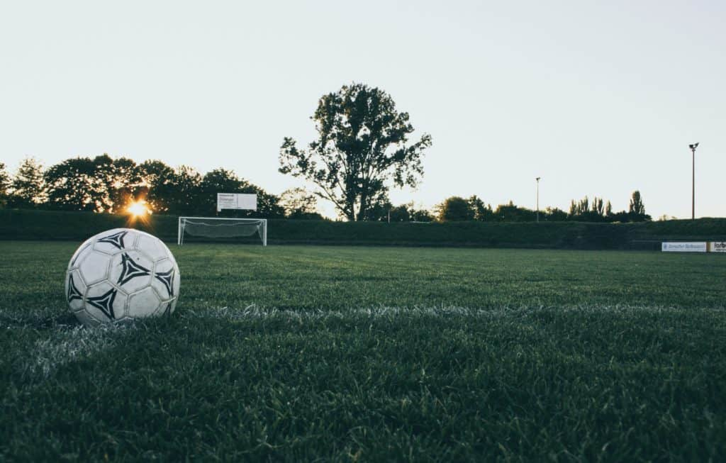 White soccer ball in the middle of the field