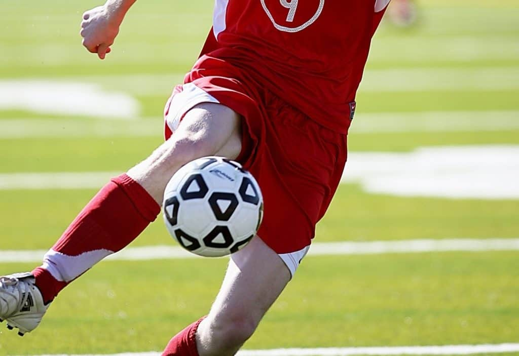 Man in a red jersey uses his shin to hit soccer ball in a match