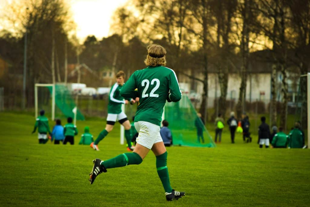 Soccer player in a number 22 green jersey running in a field