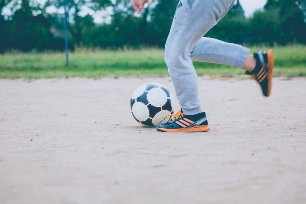 Man in blue jeans and blue shoes swung his leg to kick the soccer ball