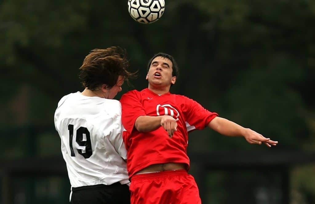 A man in a red jersey uses his head to hit soccer ball away from man in white jersey