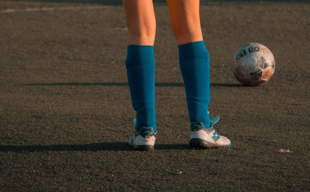 Girl in blue knee high socks stands in front of a soccer ball