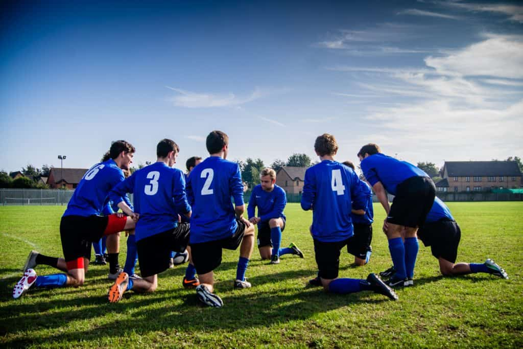 Soccer team huddled over for a meeting pre game in the field