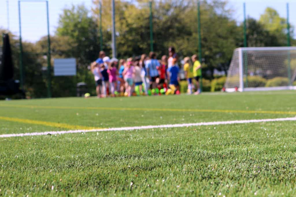 A group of young soccer players huddled over in a distance