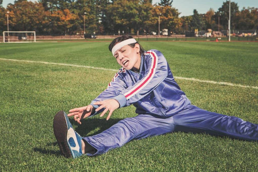 Woman athlete in a blue track suit stretches her leg in the middle of a football field