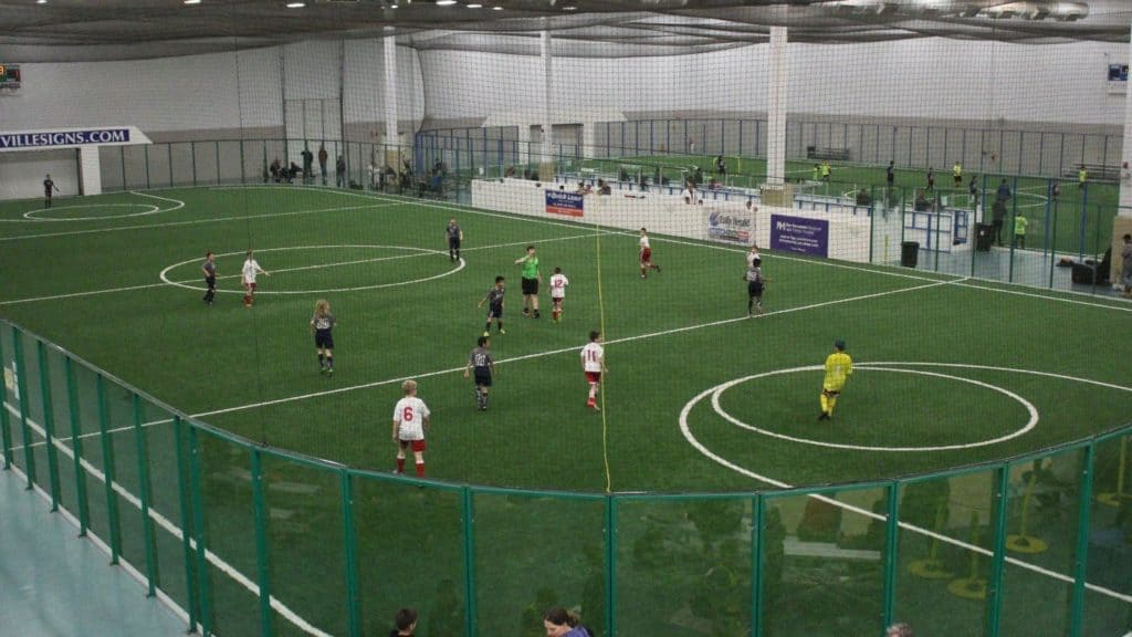 A photo of an indoor soccer field with players and teams ready in their places