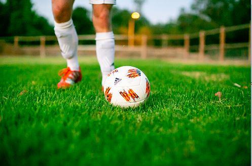 Man running next to a soccer ball
