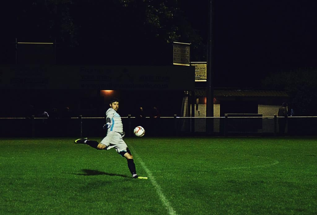 Man is preparing to kick the soccer ball in mid air