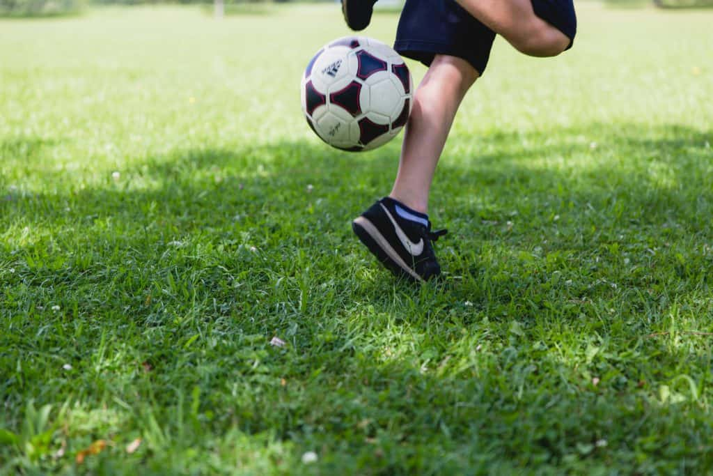 Soccer student is playing with the ball on grass