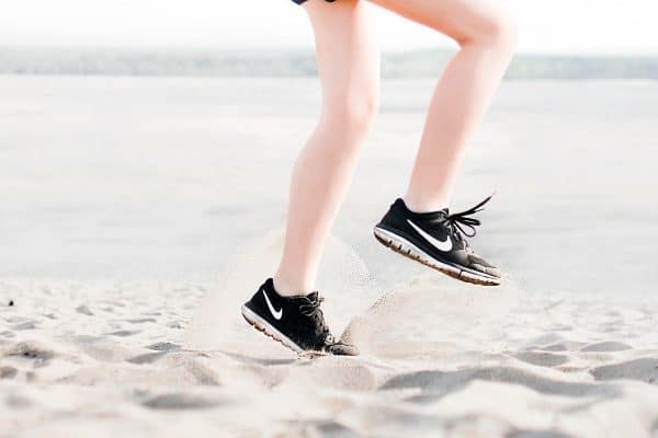 Woman wearing black Nike shoes doing knee high exercises in the sand
