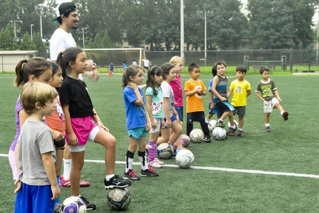 Kids lined up with a soccer ball on their feet