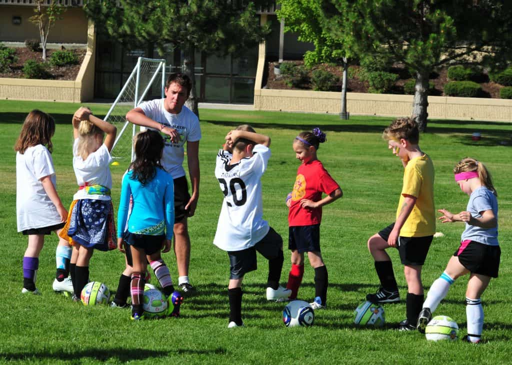 A group of kids in jerseys holding a soccer ball with their feet