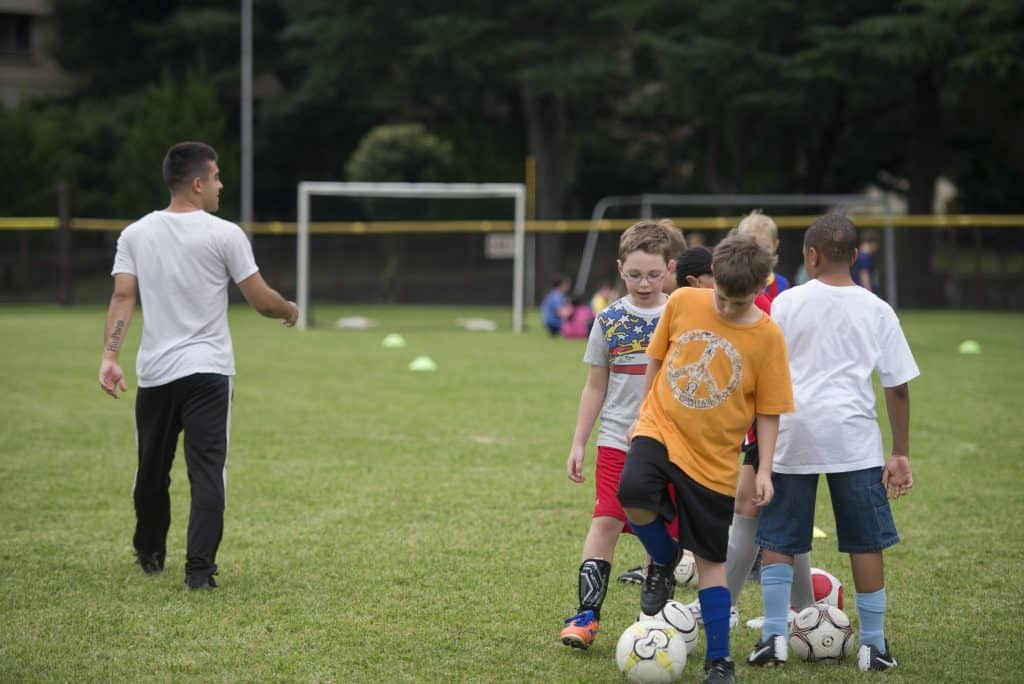 A group of kids lined up with their own balls for soccer practice