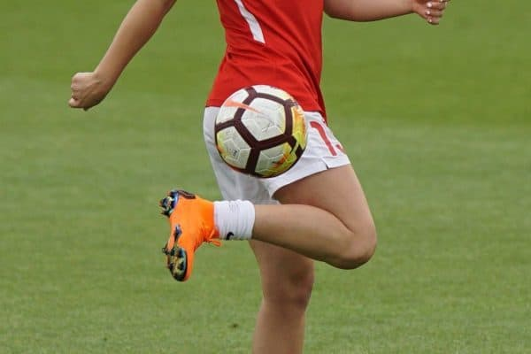 Girl in a red jersey top and white shorts juggles a white and yellow soccer ball