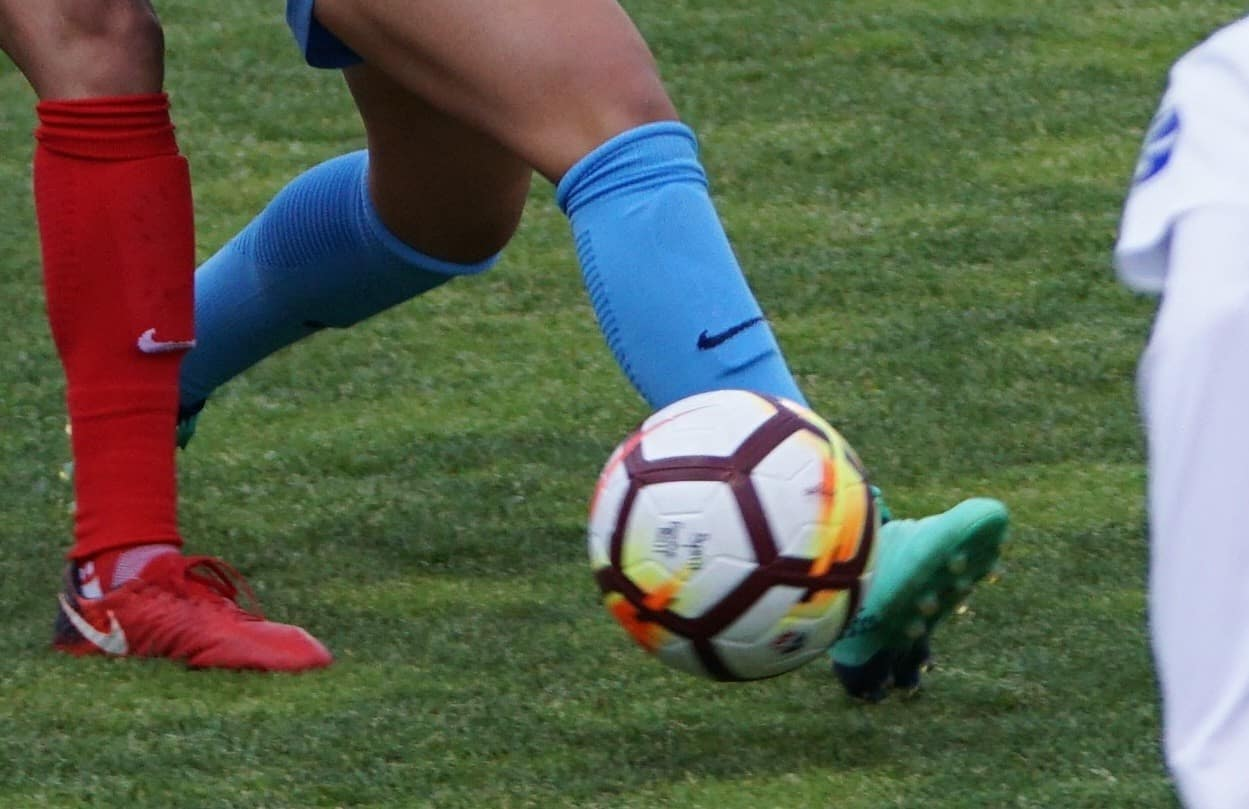 A man in blue knee high socks and teal shoes is playing with a white and black soccer ball