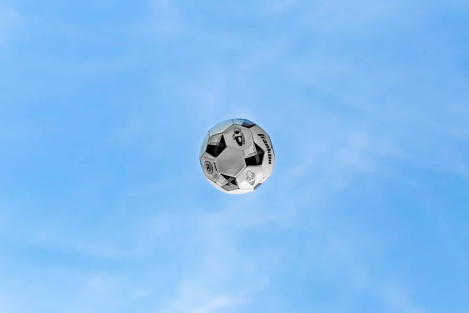 White and black soccer ball flying in the air
