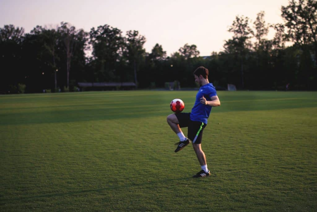 A soccer player balances a soccer ball on his thigh in the middle of the field