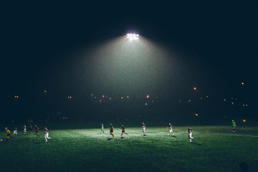 Soccer match beneath a white light in the middle of the field