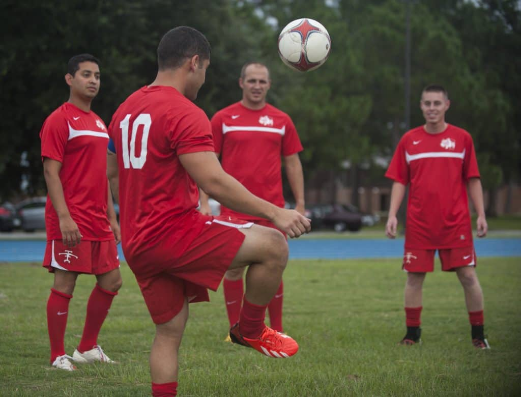 A group of soccer players in red jerseys practicig with the ball