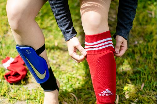 Girl putting on a red soccer sock on top of blue shin guards