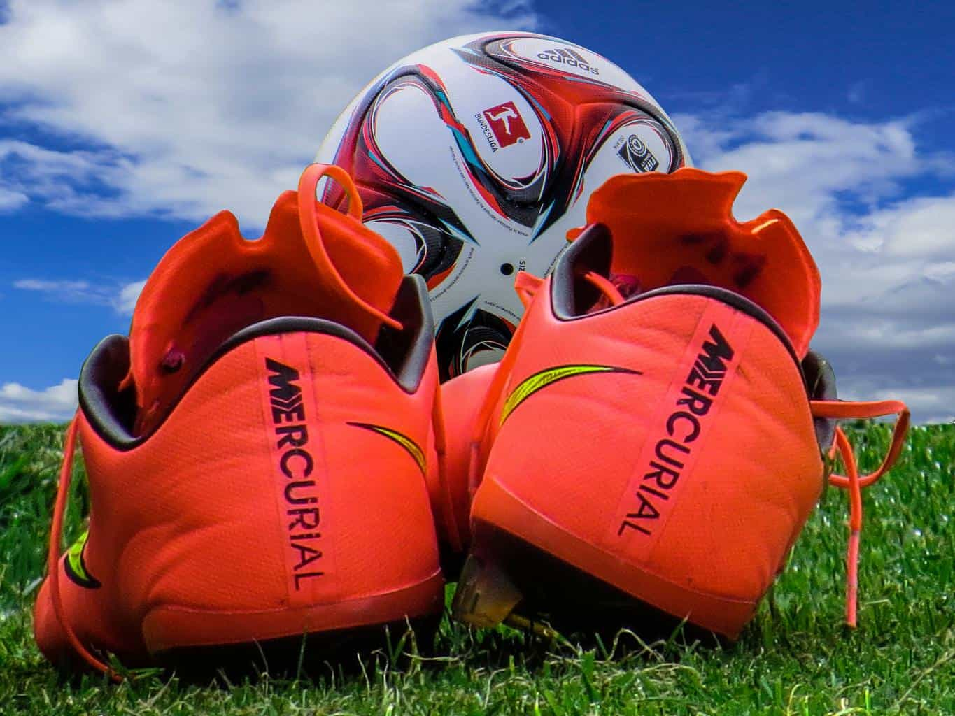 Red soccer cleats and a white soccer ball on grass