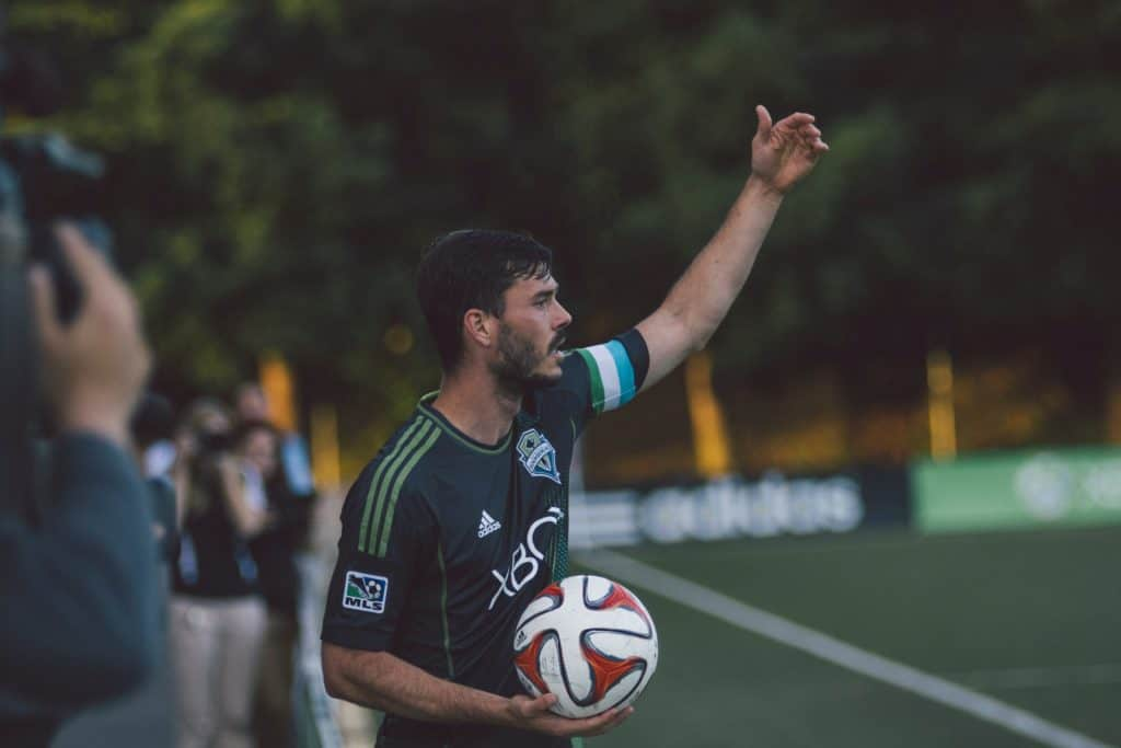 A man in a dark blue jersey holding a soccer ball in the middle of the field
