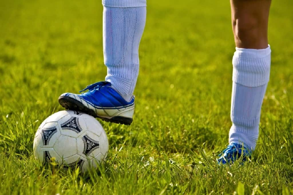 Close up of a teen's legs wearing shin guards undearneath white knee high soccer socks