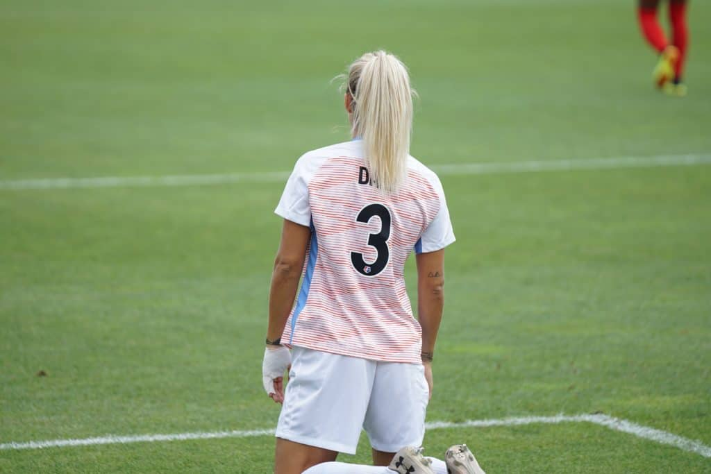 A girl with platinum hair stands with her back to the camera in a nmber 3 jersey