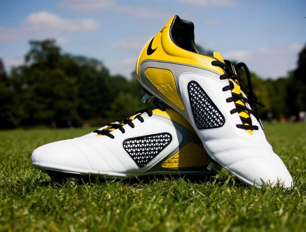 White and yellow Nike Soccer shoes on a grass field