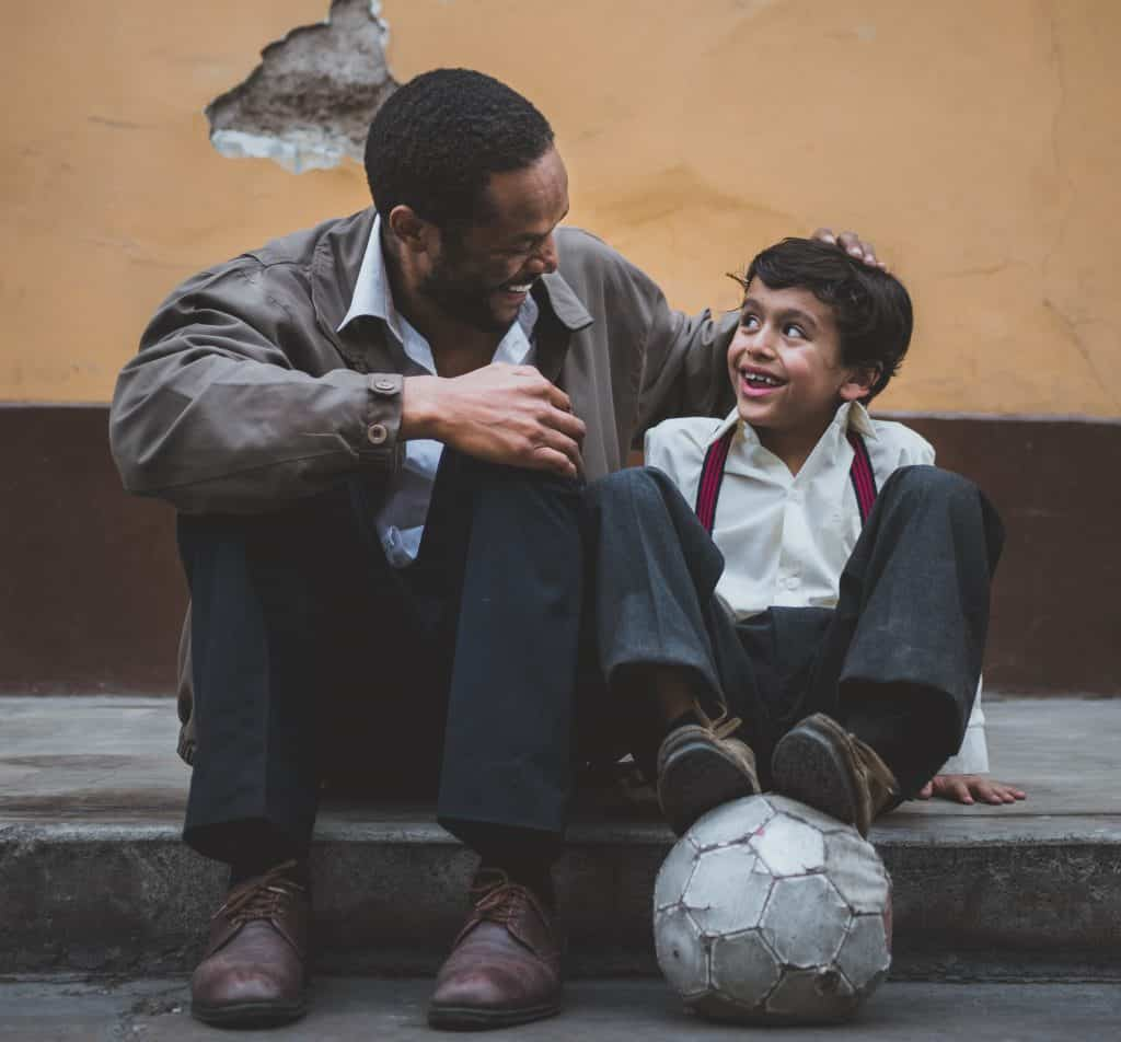 A man with his child sitting on a sidewalk laughing and smiling with a soccer ball