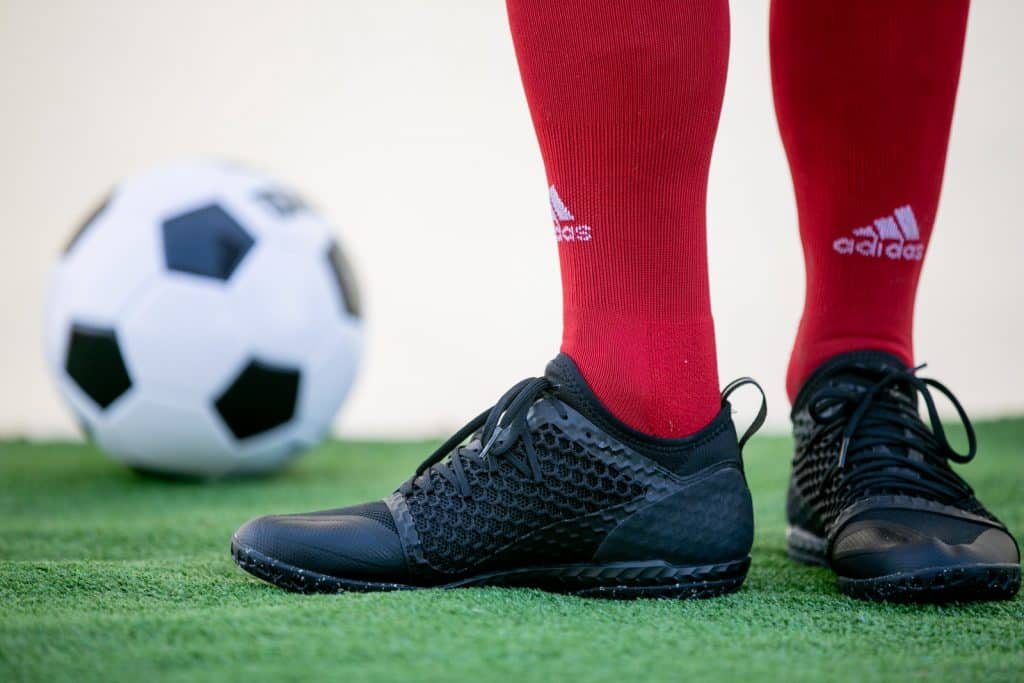 Soccer player in red socks and black indoor shoes with a soccer ball