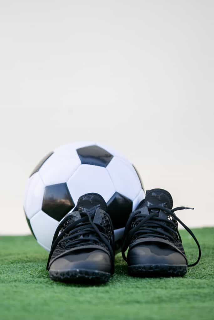 Portrait photo of a black indoor soccer shoe with a white and black soccer ball