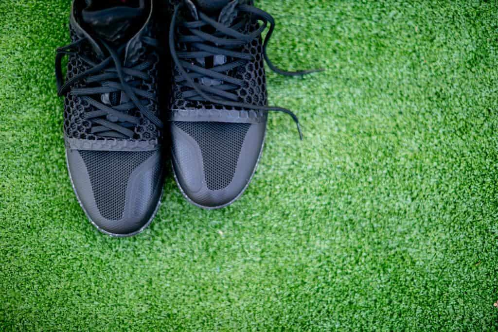 Top view of some black indoor soccer shoes on the field