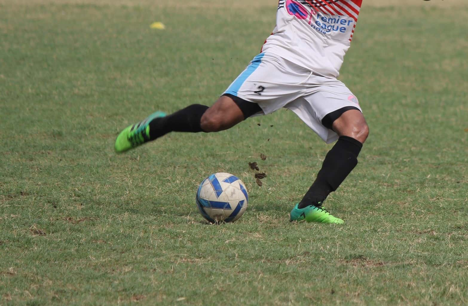 A man in a white soccer jersey is preparing to do a cross with the soccer ball