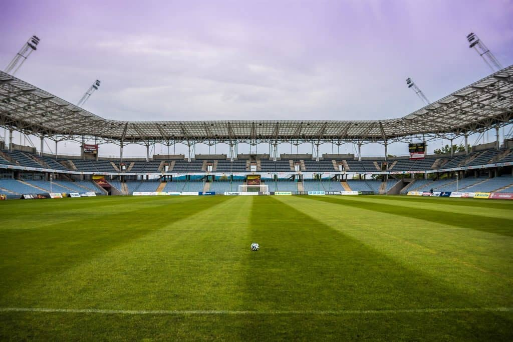 Front view of a football field with a white soccer ball in the middle