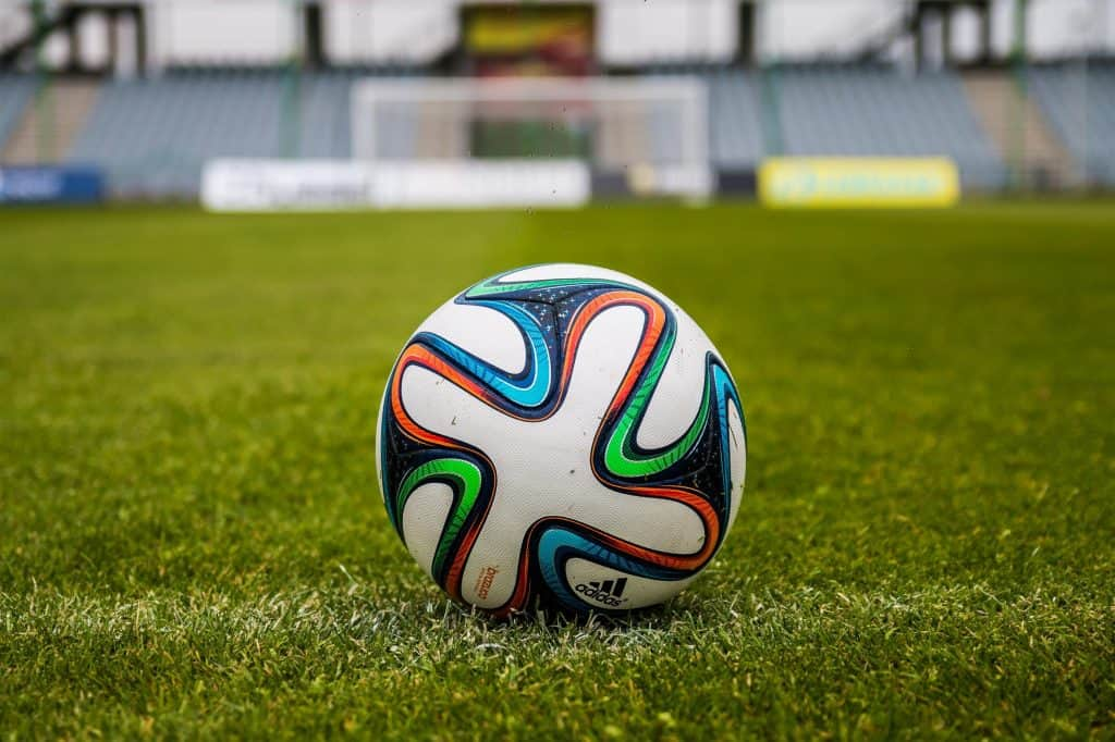 Close up of a white soccer ball in the middle of the field