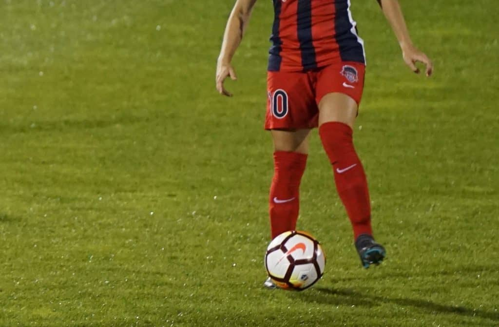 Girl in a red jersey with a white soccer ball in a field