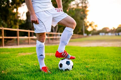 Man in white soccer jersey stepping on a soccer ball with his left leg