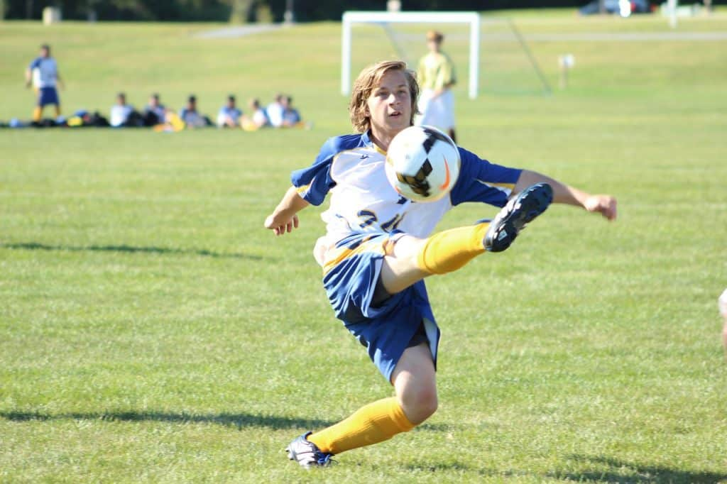 Soccer player kicking the ball while it is in the air